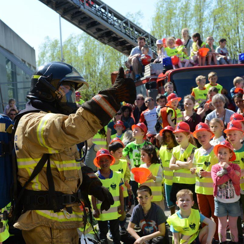 """En brandmand giver """"thumbs up"""" til en masse små børn. Alle børn er udstyret med refleksvest og hjelme"""