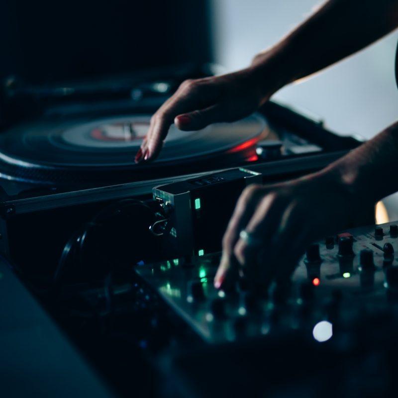 En kvinde afspiller plader på en DJ pult