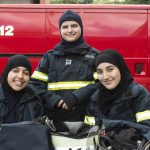 Tre unge kvindelige brandkadetter er opstillet til et billede