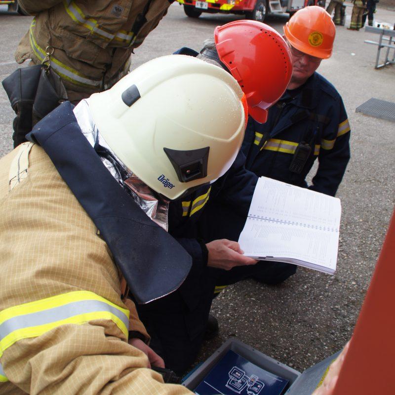 Brandmænd undersøger tekniske forskrifter i manual