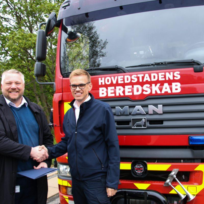 Beredskabsdirektør Jakob Vedsted Andersen og Rasmus Storgaard, beredskabschef i Beredskab Øst giver hånd foran en brandbil