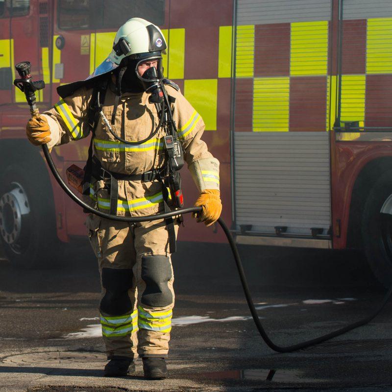 En brandmand i fuldt udstyr går med en brandslange i hånden