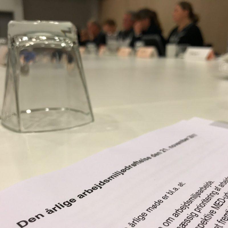 Et stykke papir om arbejdsmiljødrøftelse ligger på et bord