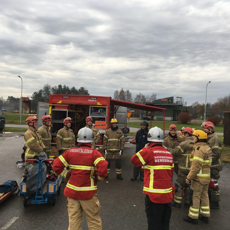 Brandmænd og indsatsledere er samlet i en rundkreds og holder møde