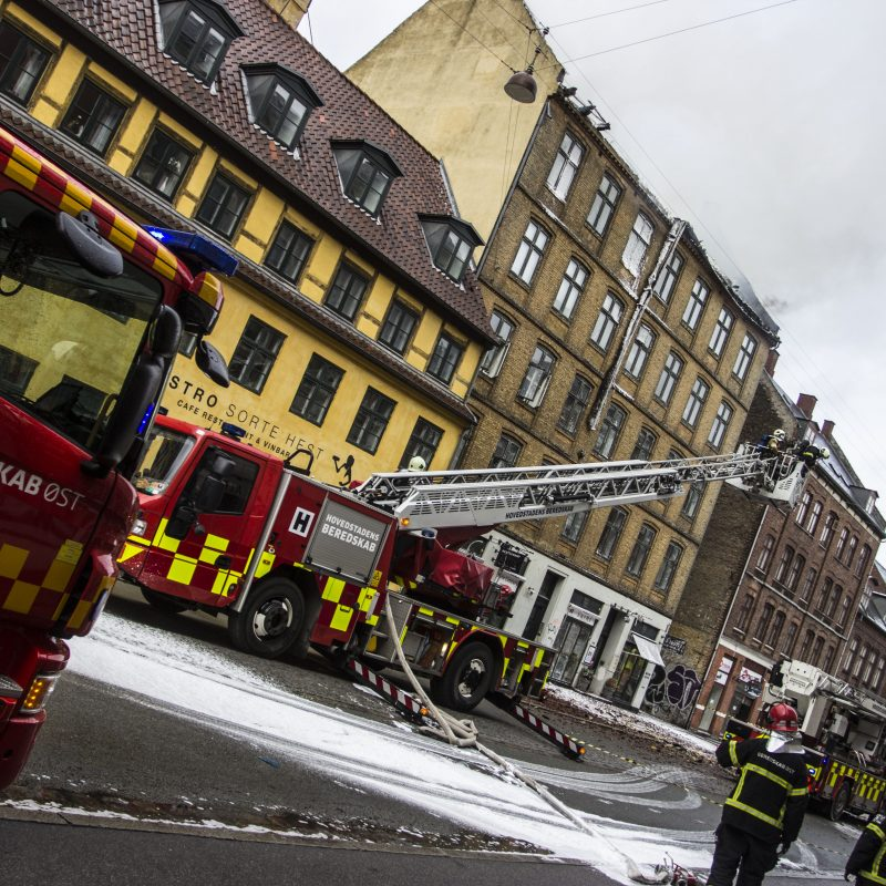 Brandbiler er opstillet på en gade. Der er skum på gaden, efter brandslukning
