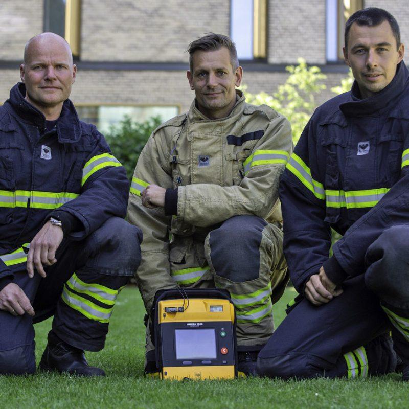 Brandmænd knæler foran en hjertestarter