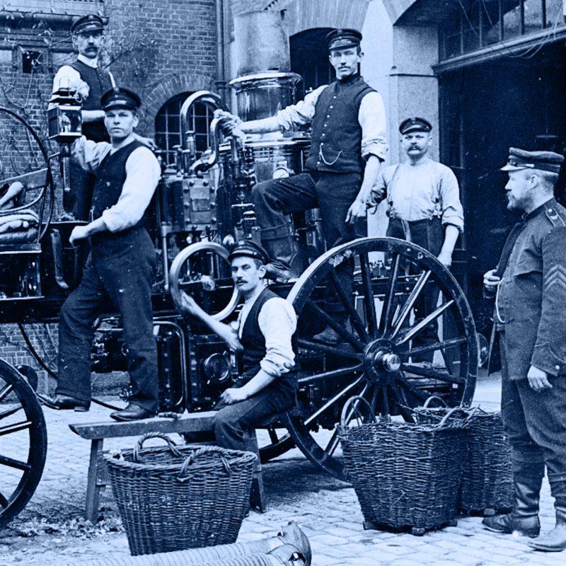 Billede af ældre dato, der viser en dampsprøjte og mandskabet der betjener den