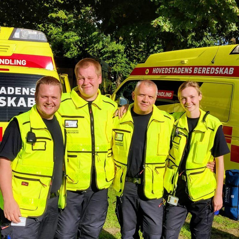 Fire frivillige, fra Frivilligeenheden, står foran to ambulancer