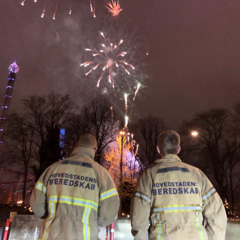 To beredskabsfolk overværer fyrværkeri nytårsaften
