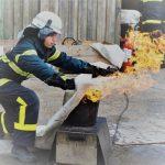 Brandkadet forsøger at slukke en brand med et brandtæppe
