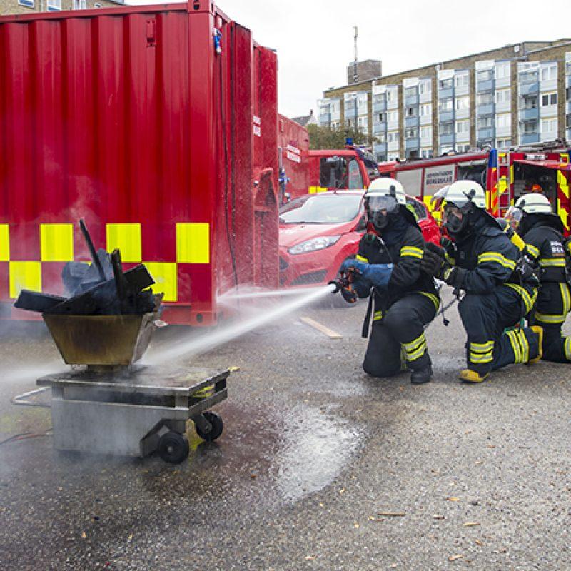 Brandkadetter øver sig på at slukke en lille brand med brandslange