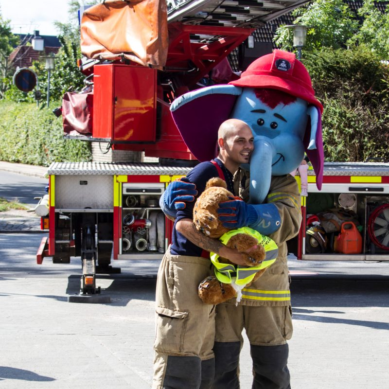 HBR's maskot Ildefanten krammer en brandmand