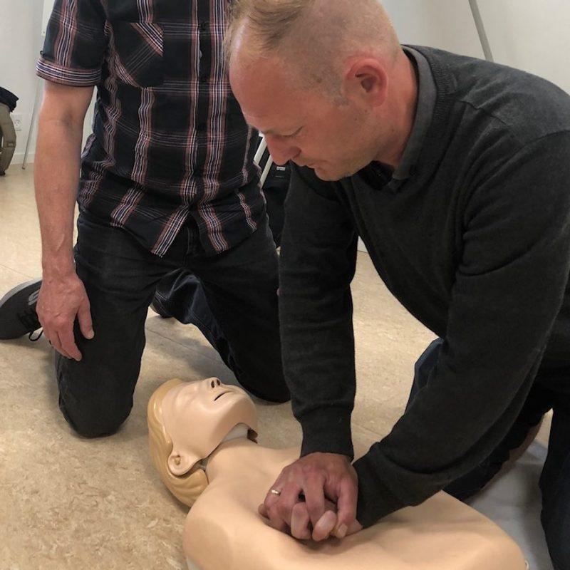 En mand udfører hjertemassage, på en øvelsesdukke. En anden kigger på