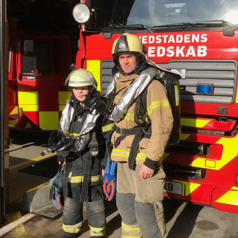 En brandkadet fra Ungdomsbrandkorpset står med en brandmand foran en brandbil
