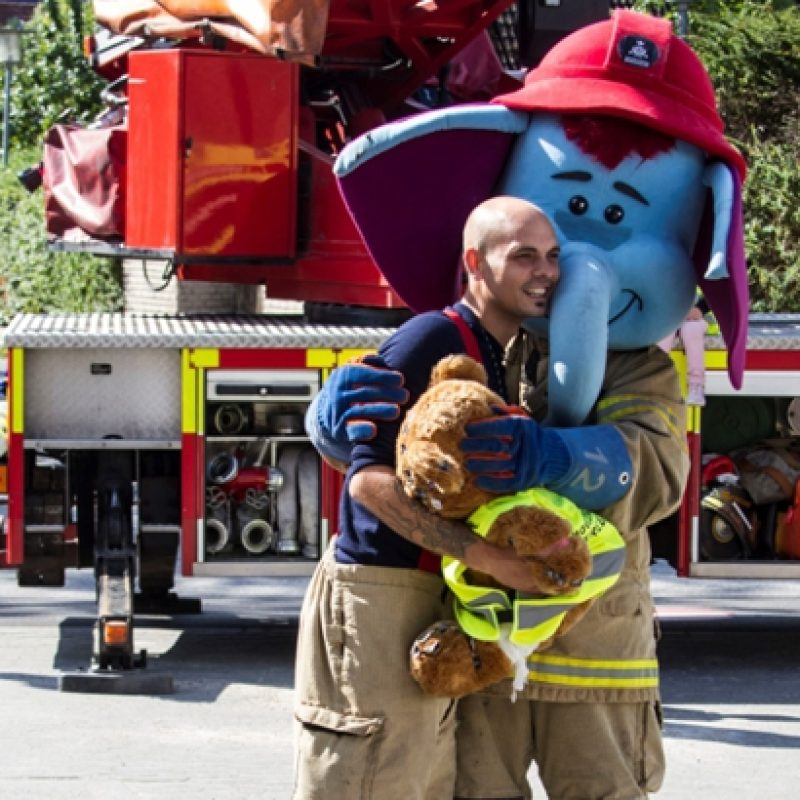 "HBRs maskot ""Ildefanten"" krammer en brandmand"