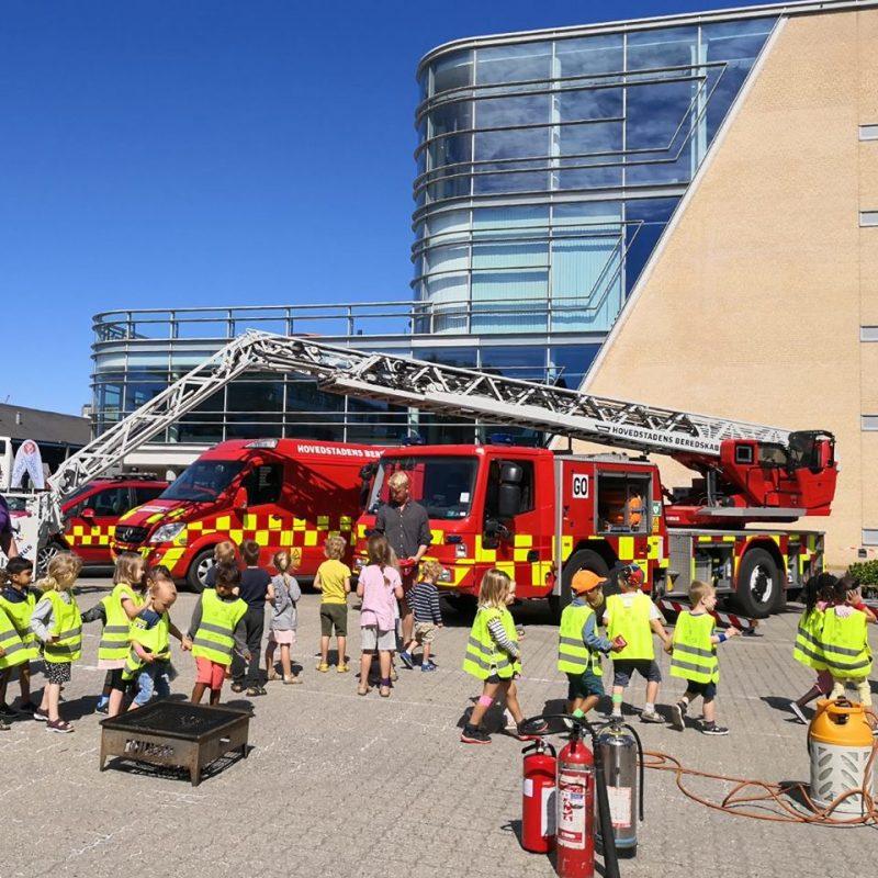 Små børn er samlet foran HBRs brandbiler til Glød og Flamme arrangement