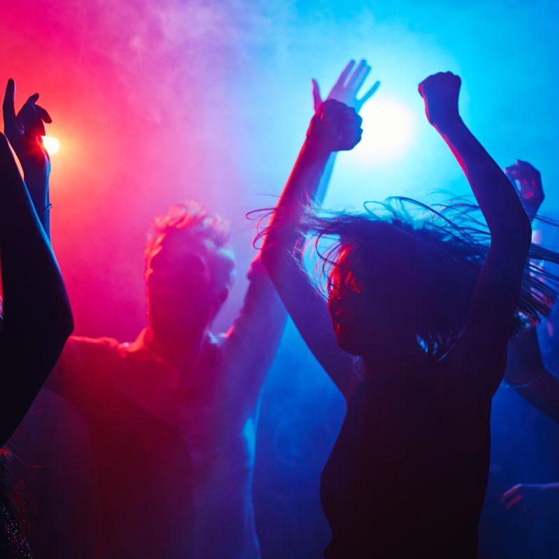Personer danser i farvet diskotekslys